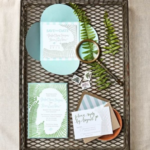 A hand-painted palm frond motif is a clever way to tie the wedding paper together and give guests a speak peek at the wedding theme.
