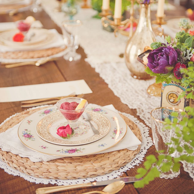 A long wooden table has a small-town communal feel. Top it with a lace runner, candlesticks, mercury glass vases of spring blooms and multilayer place settings. Here, woven chargers add a rustic touch to the delicate gold-rimmed china.