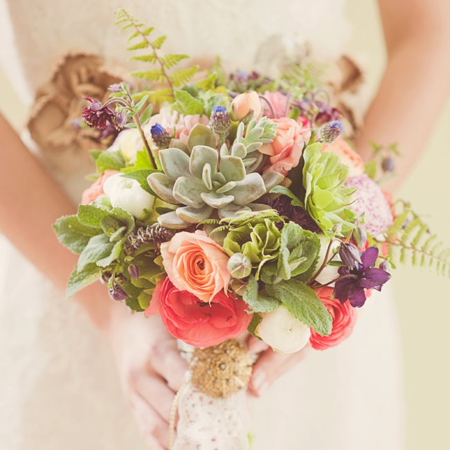 An old brooch, gold cord and antique lace add history and depth to an earthy spring bouquet. Here, a rustic mix of ranunculus, hellebore, succulents, apple mint, ferns, bachelor buttons and wild columbine feels feminine and timeless.