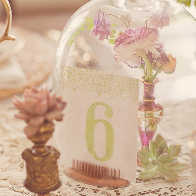 Even small details make a big impact, so make sure every bit of your wedding channels a bygone era. Look, but don't touch this sweet bell jar table number display of ranunculus and wild columbine in an antique perfume bottle. The letterpressed numbers are propped up by an old-fashioned flower frog.