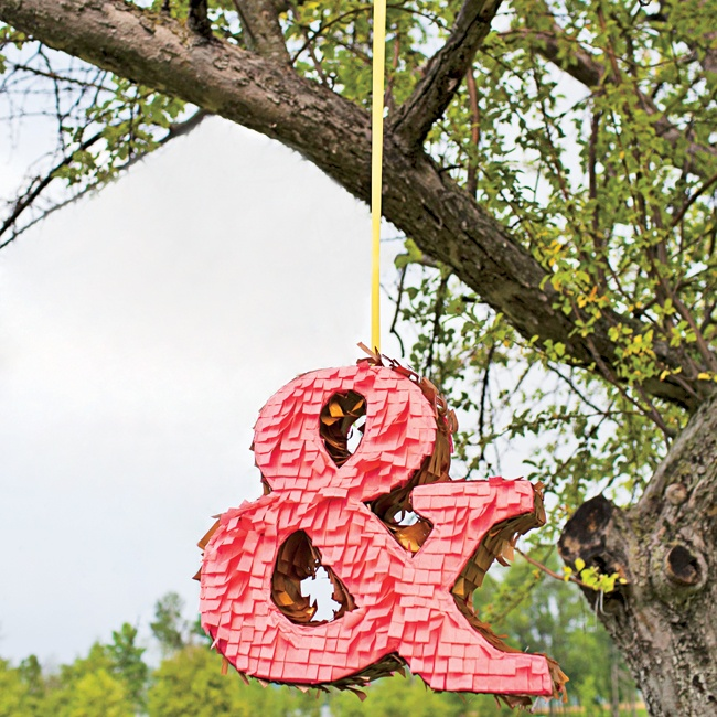 Simplify your wedding logo by using a symbol. This ampersand intimates the union of two people without actually spelling it out. We love the idea of hanging a piñata from a tree branch instead of creating a more intricate sign. Ampersand piñata by Pinyadayada.com;