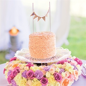 Here's a fun way to display a smaller wedding cake: Place it on a footed, cut-glass cake plate and surround the base of the plate with a ring of flowers. The ruffle-inspired frosting was piped with a single tip (read: probably less expensive than you think). Cake by Everything Gal in Traverse City, EverythingGal.com.