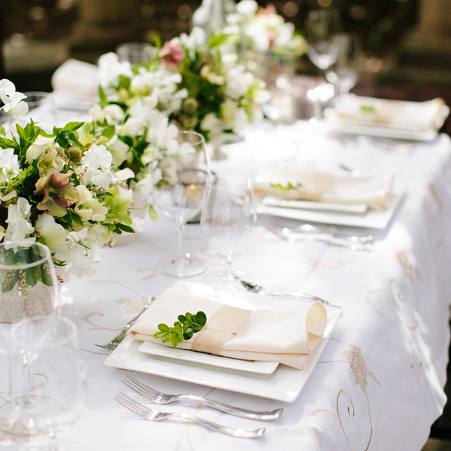 Instead of a single overflowing centerpiece, go for a few lower ones that allow guests to enjoy the venue's natural beauty. Here, it's Airlie Gardens in Wilmington. Finish with votive candles for a warm glow. Floral design by Salt Harbor Designs in Wilmington; vases and candles by Pressed Cotton in Wilmington; linens and glassware by Party Supplier ...