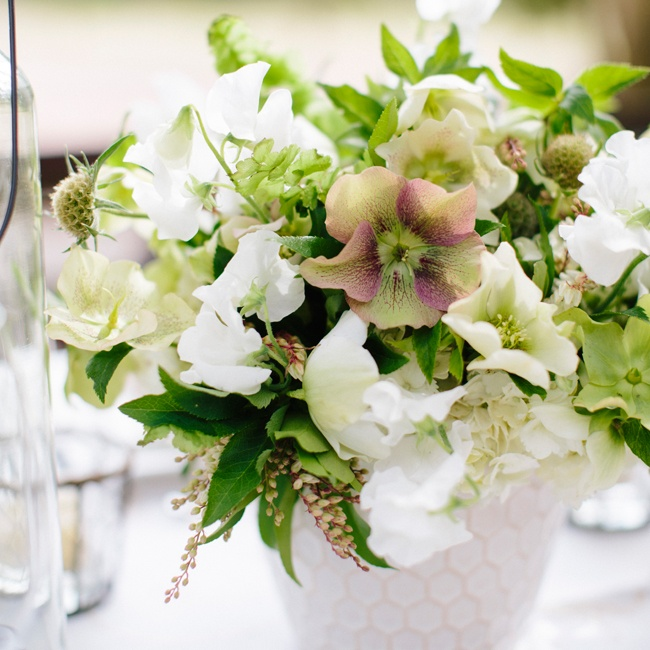 Just because you're having a garden wedding doesn't mean it has to be an English-themed one. Loose and unstructured floral arrangements placed in ceramic vases have a look that feels homemade, adding a touch of down-home Southern charm. Floral design by Salt Harbor Designs; vase from Pressed Cotton