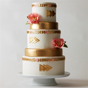 Don't be afraid to go for the gold, in a big way. Metallic details are making a comeback, and geometric appliqué triangles paired with wide bands of fondant are wonderfully en vogue. To keep the look from getting too glitzy, flowers in soft pink add a delicate balance to this glorious gold statement-making cake.