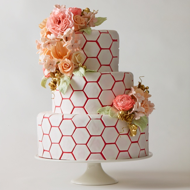It's the bee's knees! Honeycomb is a style star on the rise, making this playful pattern just perfect for a fashionable wedding cake. The simple hexagonal shapes come to life against a bold background of magenta, while lovely sugar-spun pastel peonies and roses add an irresistible flourish.