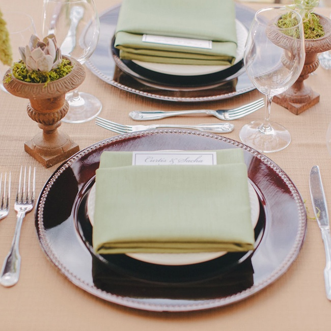 Sage green napkins, bronze chargers and terra cotta vessels set the tone for a chic Tuscan-style affair.