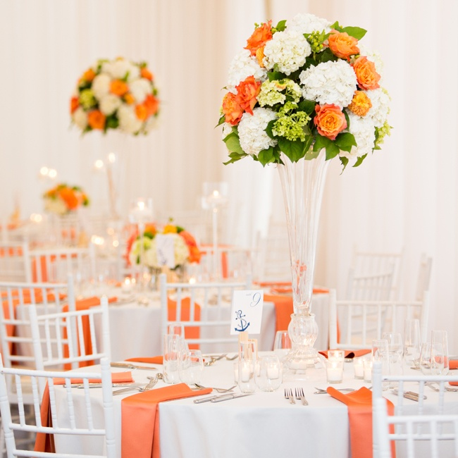 Vibrant arrangements of white hydrangeas and orange roses sat in high glass vases corresponded with the orange table linens and added an elegant flair to the reception decor. Votive candles in long-stemmed candle holders added a warm soft glow for a romantic ambiance.