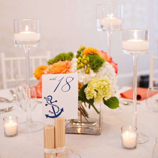 The couple incorporated the nautical theme into the table decor with navy and white table number cards featuring anchors. The cards were propped up by little wooden posts tied with rope to resemble a marina dock.