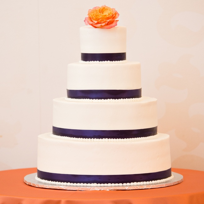 Navy ribbon and buttercream pearls adorned each layer of the couple's elegant wedding cake. The cake was topped with a single orange peony.