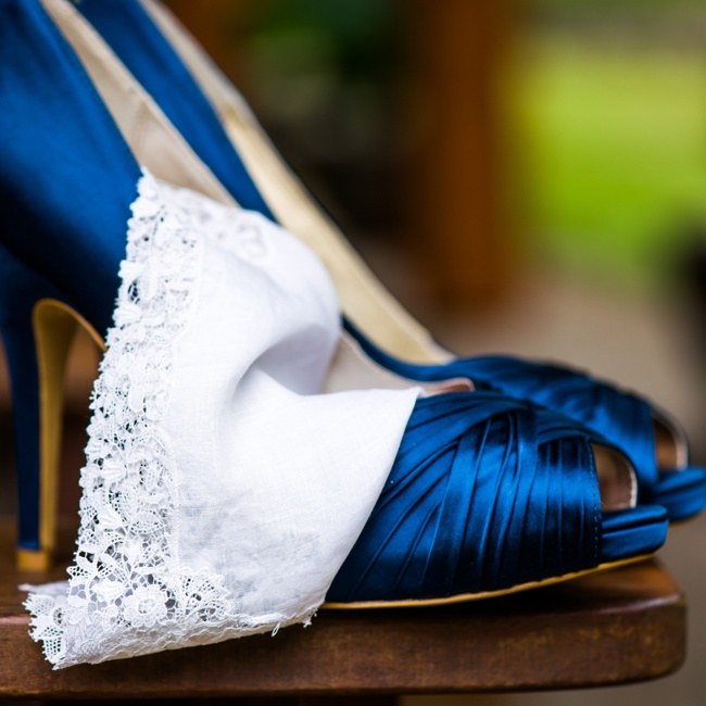 The bride wore dark blue satin peep-toe pumps.