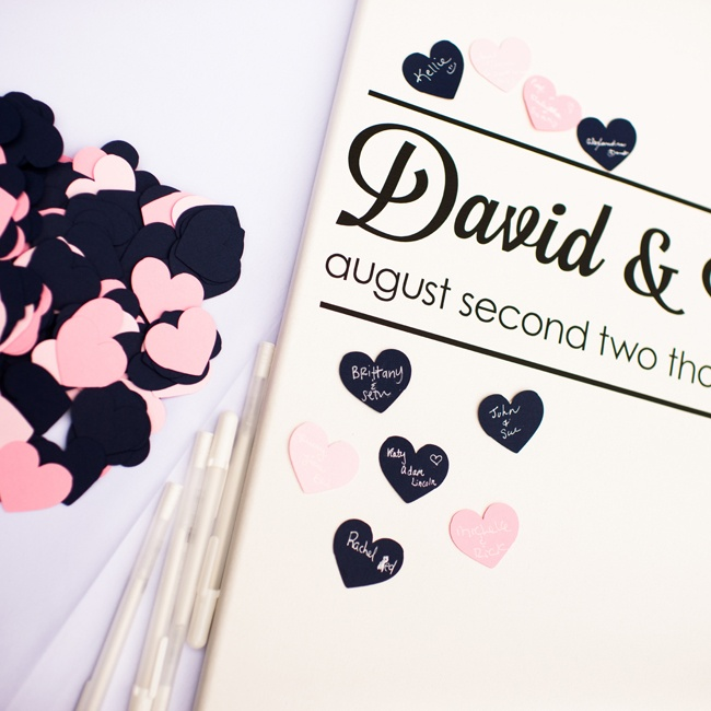 As an alternative to the traditional guest book, guests wrote on pink and black paper hearts to leave wishes for the couple.