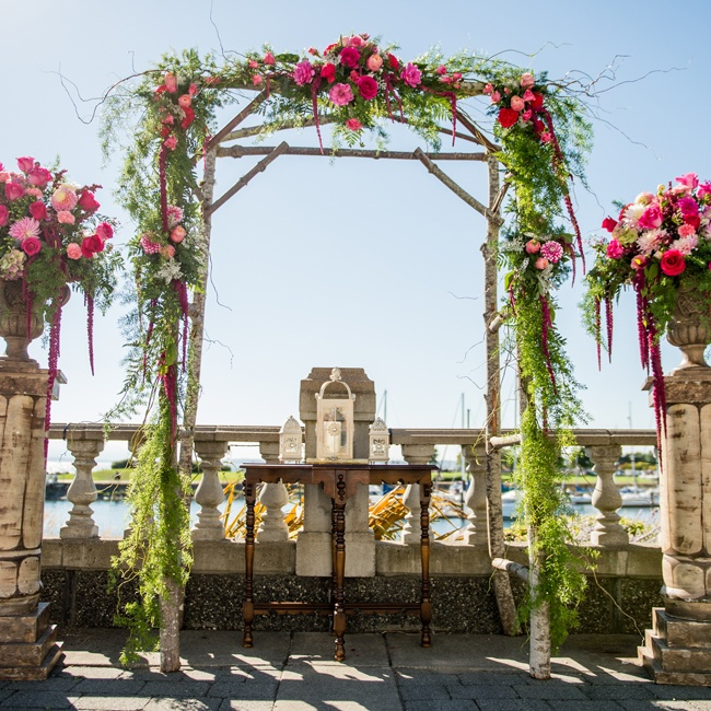 A wedding arch made up of pink roses and ferns made for a beautiful focal point at the ceremony.