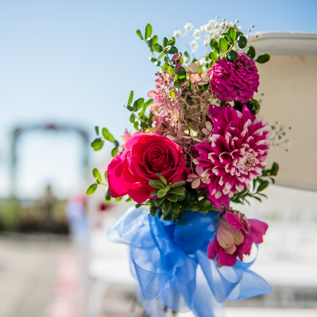 Dahlias and rose arrangements incorporated the couple's pink and blue color palette at the ceremony.