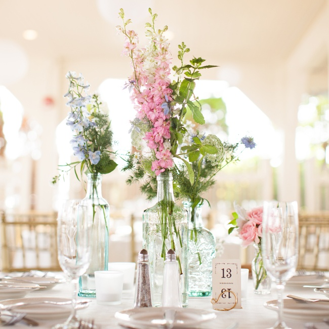 Simple wildflower arrangements in pinks and purples filled decorative glass bottles and vases for a feminine, vintage air.
