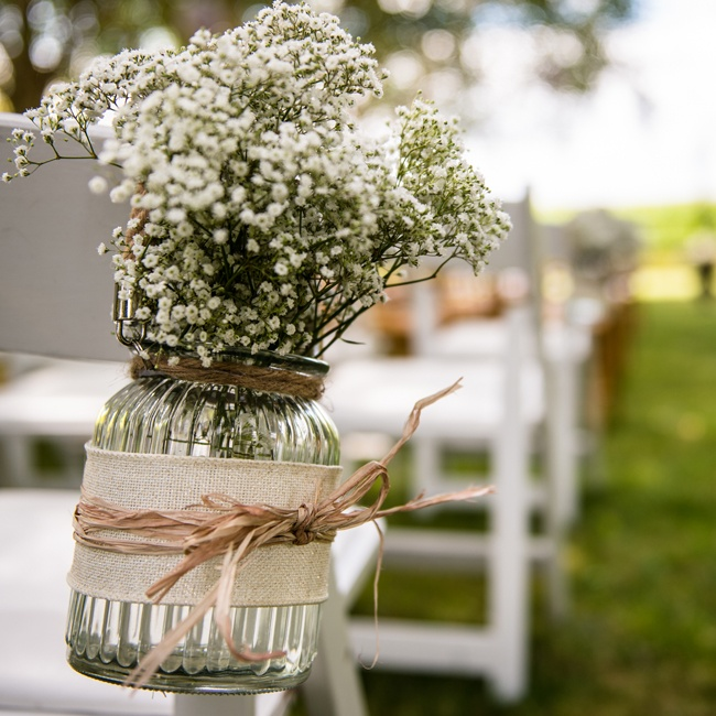 Jars of baby's breath decorated the aisles at the outdoor ceremony.