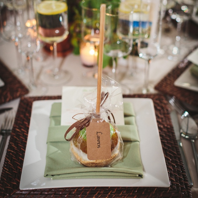 Caramel apple favors for guests sat on top of a modern tablescape with wooden chargers.