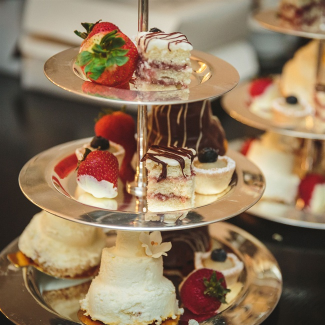 An array of desserts, including chocolate-covered strawberries and layered cake, were set on a modern silver stand.
