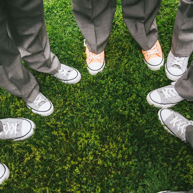 The grooms kept their look casual by wearing Converse with their gray suits.