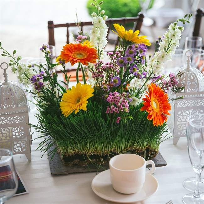 For a twist on the traditional centerpiece the couple used a living arrangement of grass, daisies, hyacinth and stock.