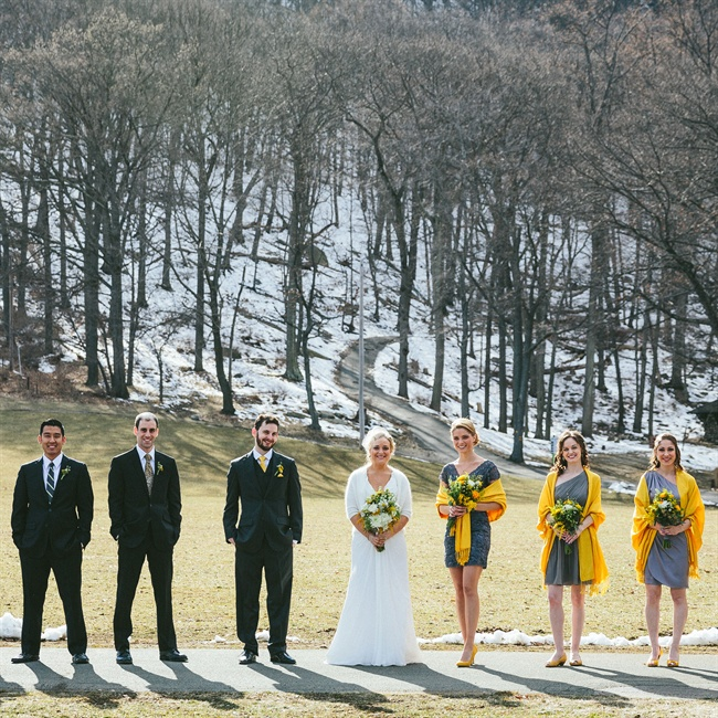 Bridesmaids wore short gray dresses and accessorized in yellow wraps while groomsmen wore charcoal suits.