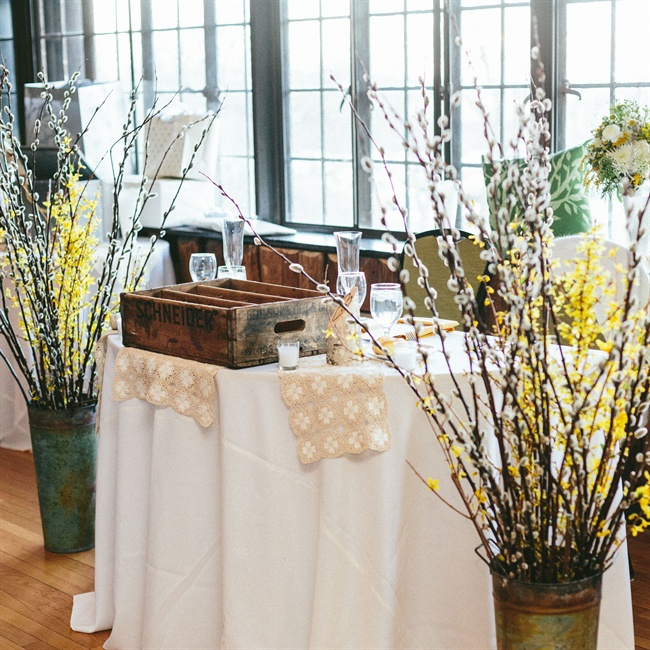 The couple's sweetheart table was set with vintage crates and flanked by tall arrangements of pussy willow branches.