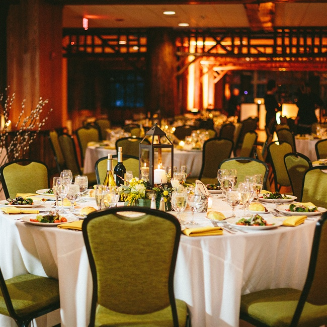 Green chairs and yellow place settings complemented the couple's rustic design aesthetic.