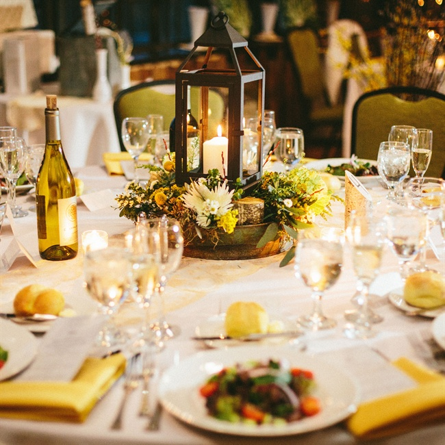 Candlelit lanterns surrounded by flowers made for interesting centerpieces at the reception.
