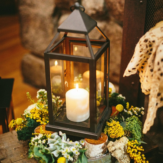 Reception decor included lots of candles and lanterns set up on birch branches and floral arrangements of yellow fernleaf yarrow and white daisies.