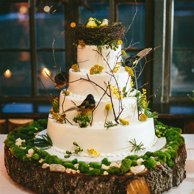 The couple's wedding cake was topped with birds, tree branches and yellow flowers.