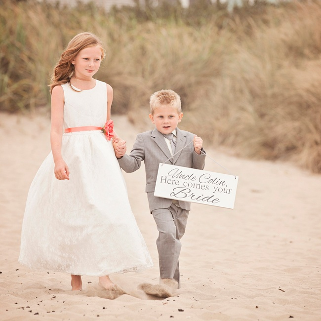 "Young relatives of the bride and groom walked barefoot down the aisle as flower girls and ring bearers. One ring bearer carried a sign that read, ""Uncle Colin, Here comes your bride."""