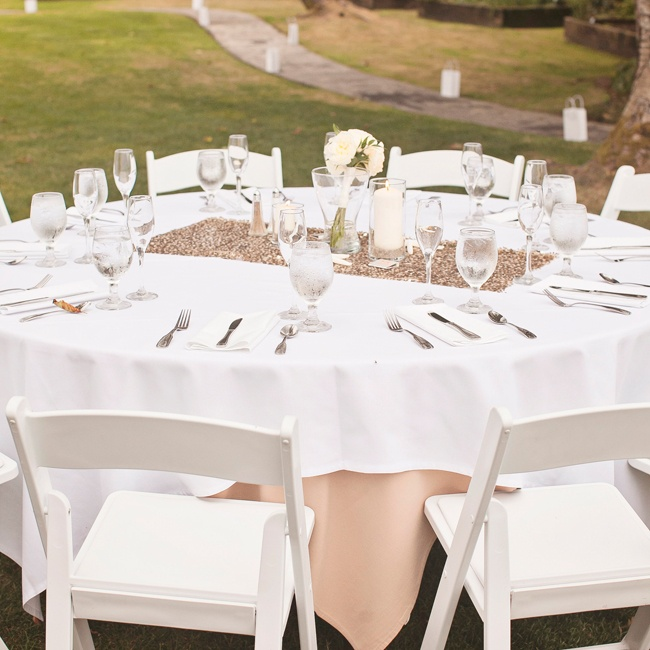 Tables were decorated with neutral tablecloths in tan and white, then topped with a metallic, sequined table runner and set with traditional silver and glassware.