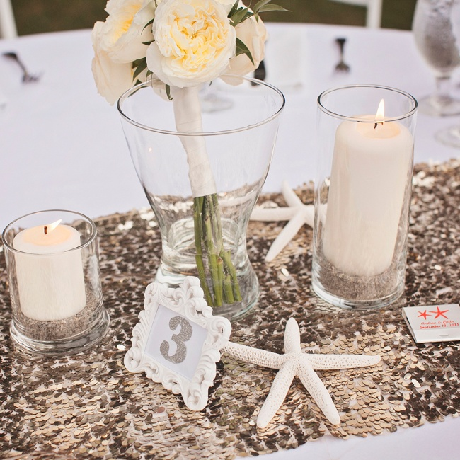 Table centerpieces included a bouquet of peonies surrounded by pillar candles and starfish on top of a sequin table runner.