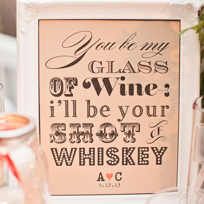 "The bar was decorated with flowers and signs in white picture frames that read, ""You be my glass of wine, I'll be your shot of whiskey,"" with the couple's date and initials."