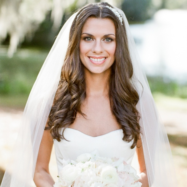 Megan wore her hair down in loose, soft curls and accessorized with a white veil.