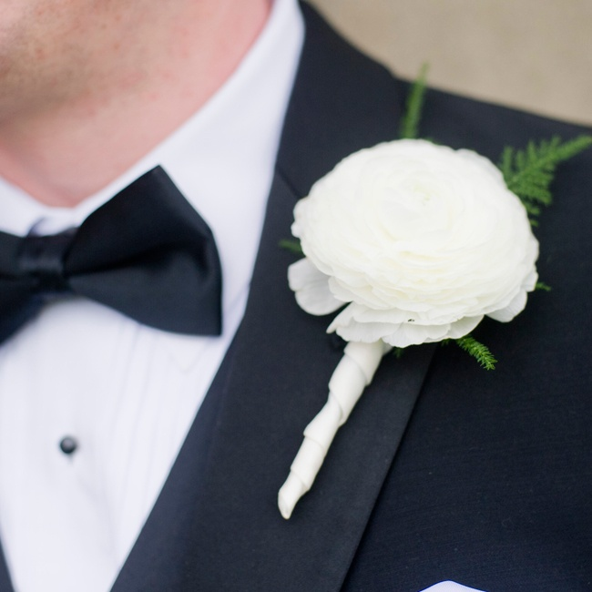 The groom wore a single white ranunculas as a boutonniere on his wedding day.