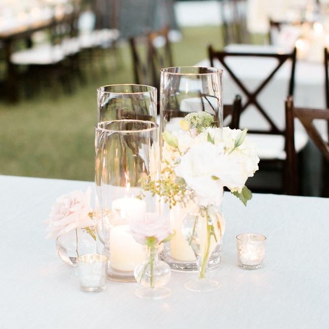 Differently shaped vases contained candles and flowers of varied sizes to create intriguing centerpieces at the reception.
