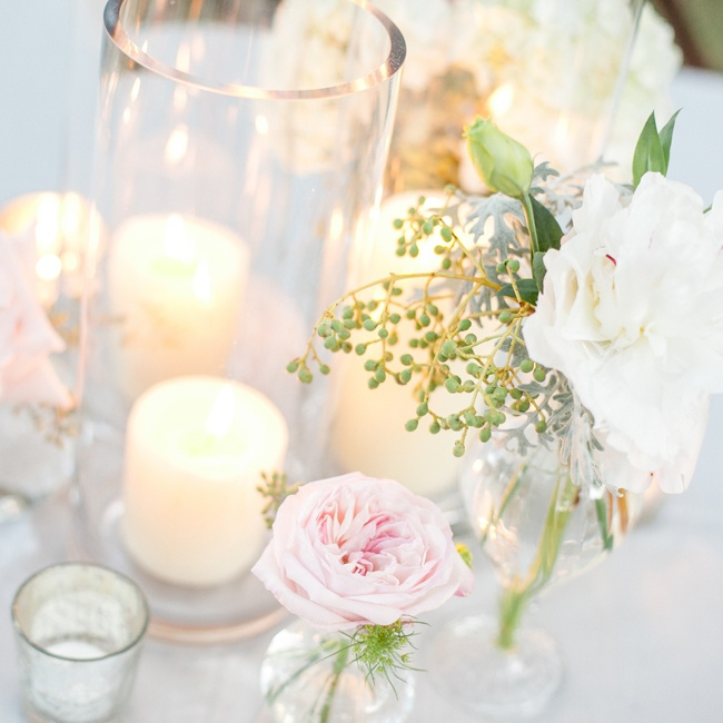 Alongside the candles and glass vases, soft pink peonies and white garden roses made romantic centerpieces.