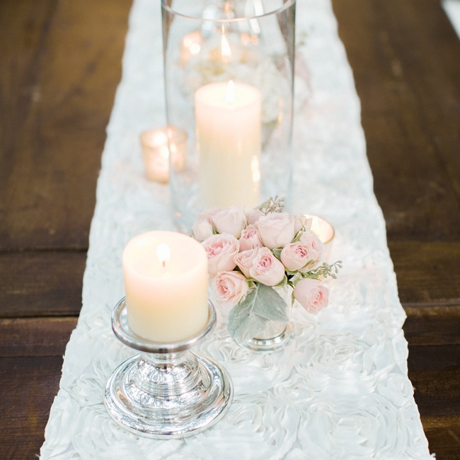 The dark wooden tables were lined with a white rosette table runner and candles of different shapes and sizes.