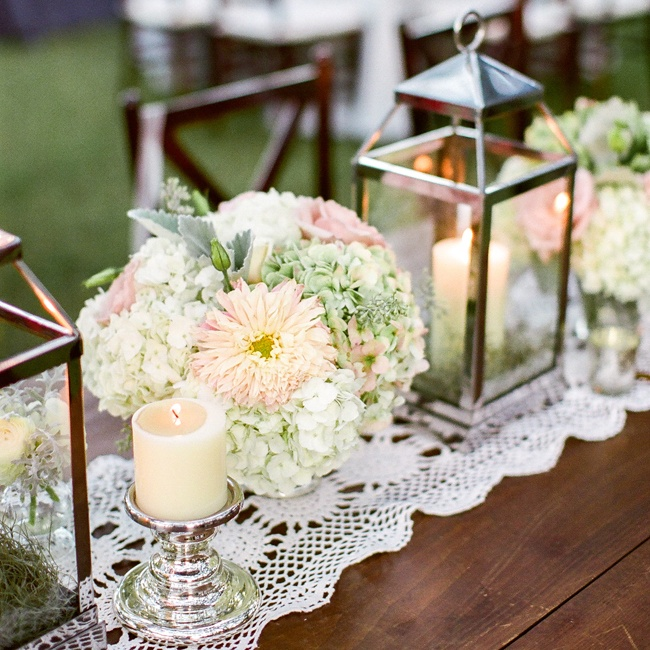 The couple used metal lanterns lit with candles among the green and white hydrangea arrangements as romantic centerpieces.
