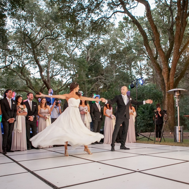 The couple celebrated their first dance as newlyweds on top of a black and white outdoor dance floor.