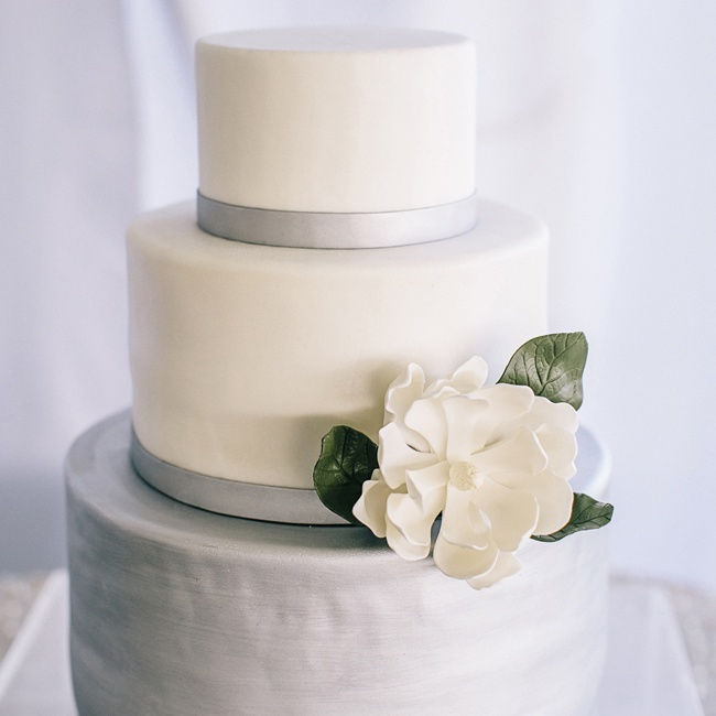 Brushed platinum details and an oversize sugar magnolia glammed up Courtney and David's vanilla fondant cake.