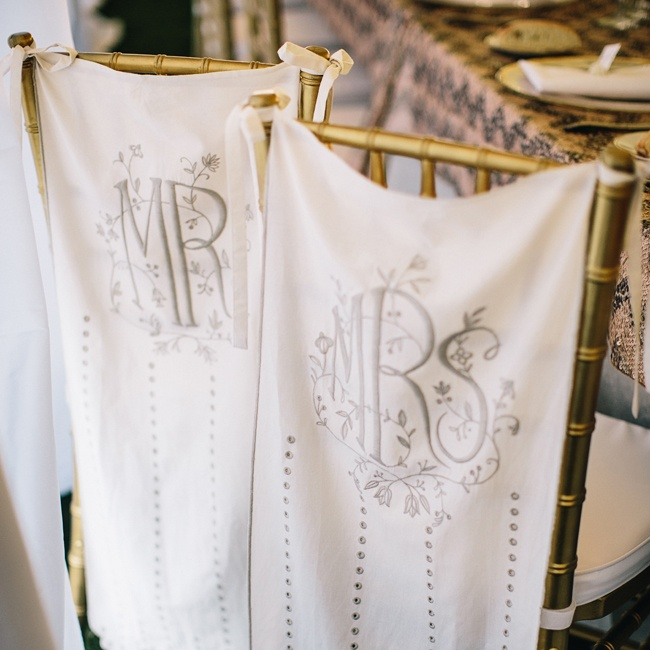 "Vintage- inspired ""Mr."" and ""Mrs."" banners hung from the back of the newlyweds' chairs at the tented reception."