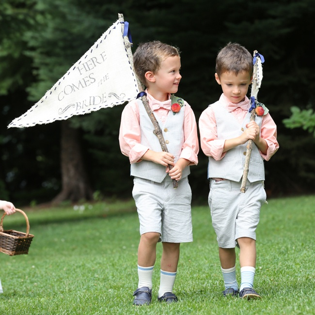 "Two young relatives of the bride and groom carried homemade ""Here Comes the Bride"" flags on sticks. They wore pink shirts with matching pink bowties and pale blue shorts and vests."