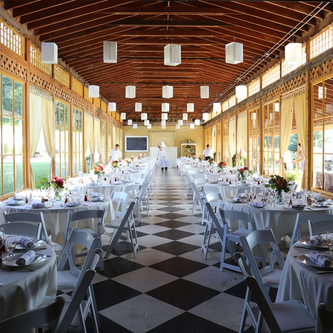 The reception space was one long hall with checkerboard flooring. Round tables were placed in two long columns with white chairs and tablecloths.