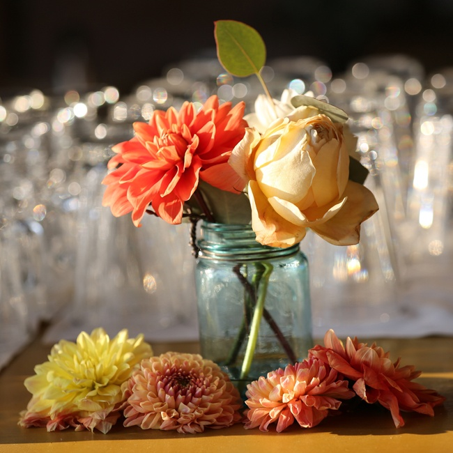 The couple used Mason jars as vases and filled them with dahlias and roses to add color to the reception site.