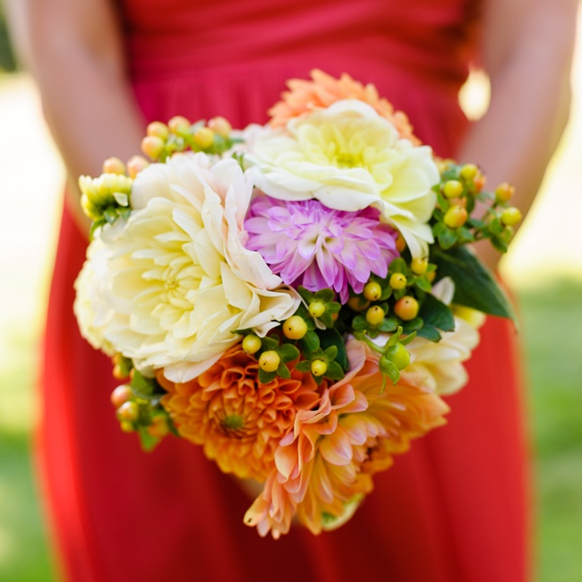 The bridesmaids carried bright bouquets with pink, orange and white dahlias, mums and zinnias with coffee berry accents.