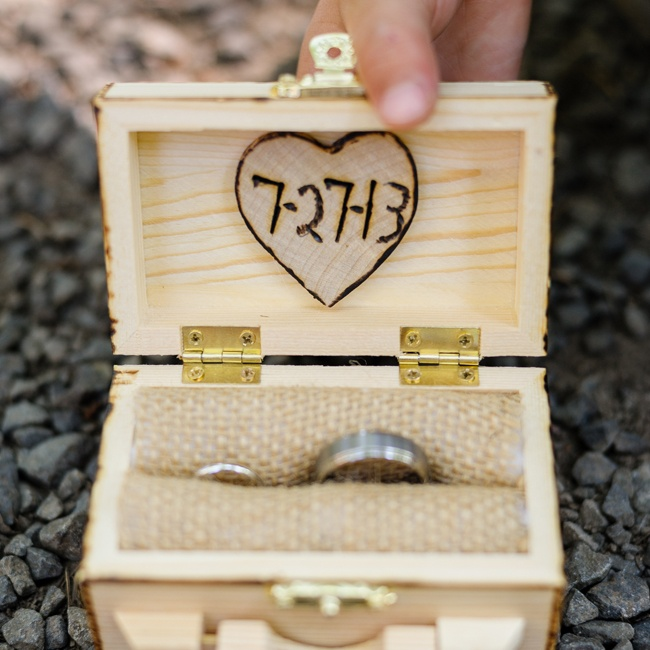 The couple's wedding rings were brought down the aisle tucked into a burlap lined wooden box. A heart was carved into the inside of the box with the date of the wedding for a rustic touch.