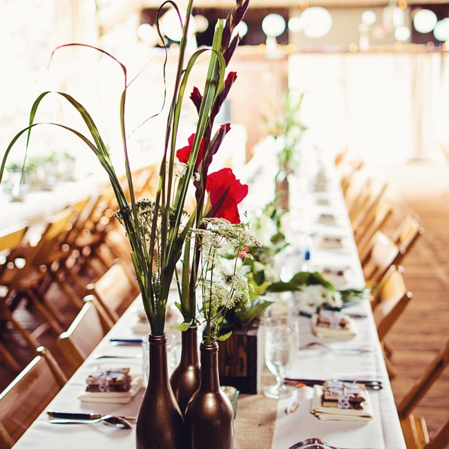 Red daffodils in rustic metallic vases decorated the barn reception space.