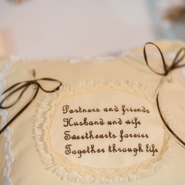 The bride and groom's wedding rings were carried down the aisle on an embroidered pillow with brown ribbons.